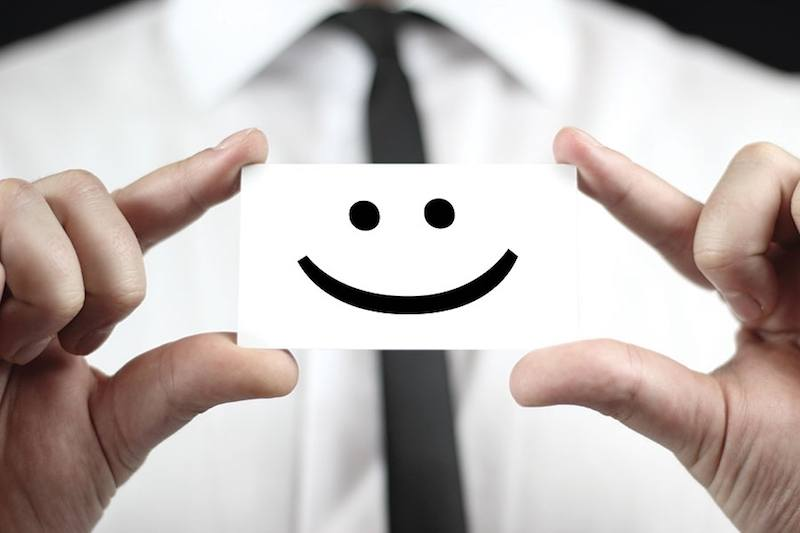 corporate man holding a card with a smile