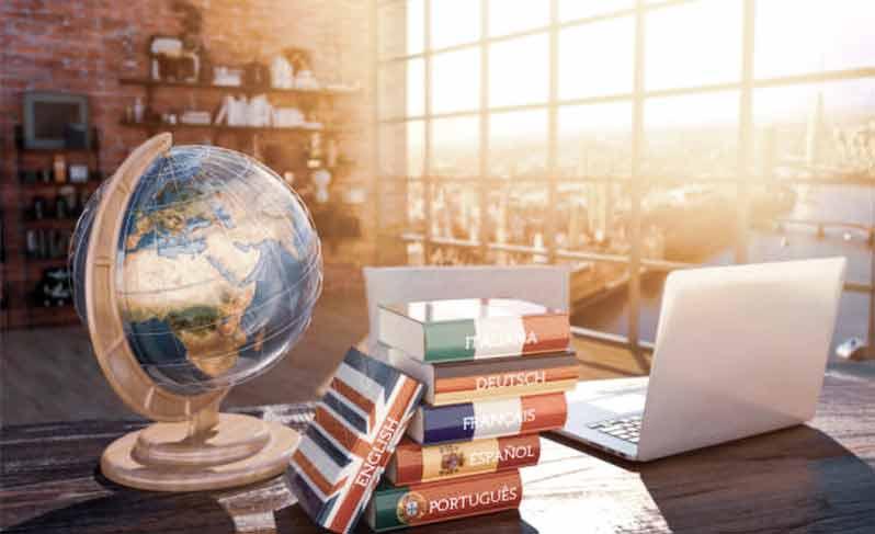translator books on a desk with a globe and a laptop